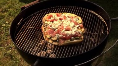 Pizza topped with courgettes on barbecue — Stock Video