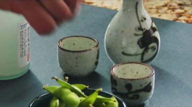 Soya beans with salt and sake bottle and cups — Stock Video