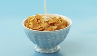 Pouring milk over cornflakes — Stock Video