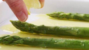 Hand sprinkling asparagus with lemon juice — Stock Video