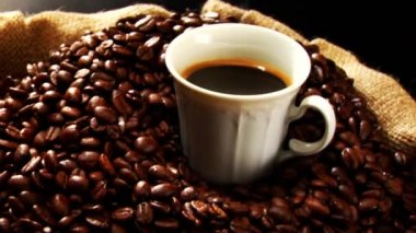 Steaming cup of coffee and coffee beans — Stock Video