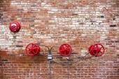 Red Sprinkler Valves against Red Brick Background — Stock Photo