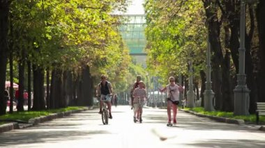 People ride a bike,skateboard,scooter in Gorky Park in the summer — Stock Video