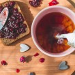 Cup of tea pouring milk, fresh baked healthy bread with blackcurrant jam - homemade marmalade with fresh organic fruits from garden. rustic decoration, fruit jam on wooden table background, breakfast. — Stock Photo #68724773