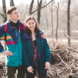 Young beautiful happy hipster couple brunette girl and guy having great fun time while travelling and walking in the woods forest — Stock Photo #68725193