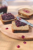 Fresh baked homemade healthy bread with blackcurrant jam - homemade marmalade with fresh organic fruits from garden. In rustic decoration, fruit jam on wooden table background. Perfect sweet breakfast — Stock Photo