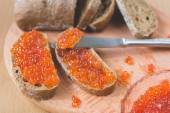 Red caviar toasts sandwich with silver knife, bowl of tasty red caviar with spoon and fresh baked homemade healthy bread on a wooden table background — 图库照片