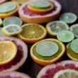 Cutted citrus mix lemon grapefruit lime and orange in geometrical shapes on dark wood rustic background  soft focus overhead-angle shot — Stock Photo #75636383