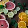 Cutted citrus mix lemon grapefruit lime and orange in geometrical shapes on dark wood rustic background  soft focus overhead-angle shot — Stock Photo #75636703