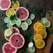 Cutted citrus mix lemon grapefruit lime and orange in geometrical shapes on dark wood rustic background  soft focus overhead-angle shot — Stock Photo #75636705