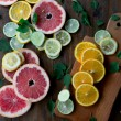 Cutted citrus mix lemon grapefruit lime and orange in geometrical shapes on dark wood rustic background  soft focus overhead-angle shot — Stock Photo #75636729