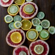 Cutted citrus mix lemon grapefruit lime and orange in geometrical shapes on dark wood rustic background  soft focus overhead-angle shot — Stock Photo #75643803