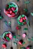 Strawberry mint infused water decorated in rustic style on dark wood table background — Stock Photo