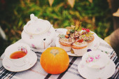 Tea in cups and teapot, cupcakes and pumpkin on the table — Stock Photo
