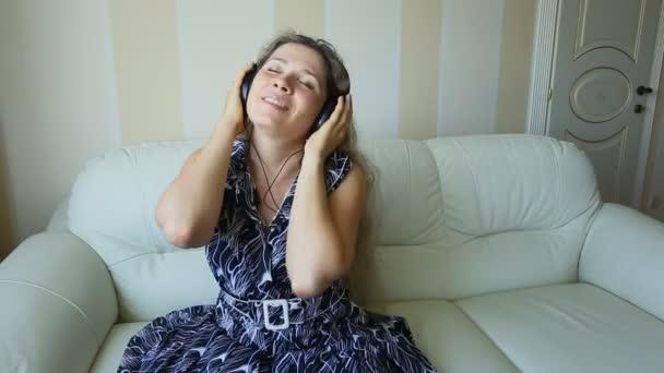 Joven hermosa mujer vestida brillante disfrutando de la música en casa — Vídeo de stock