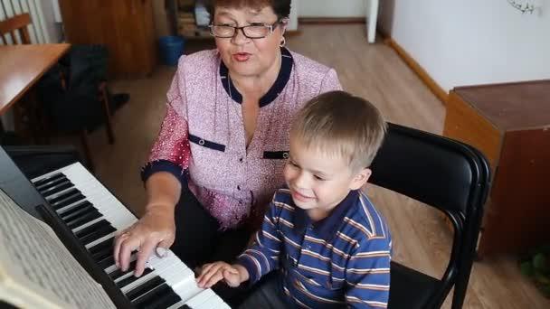 Niño aprender cómo tocar el piano — Vídeo de stock