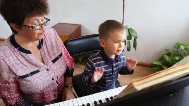 Boy learning how to the play piano — Stock Video
