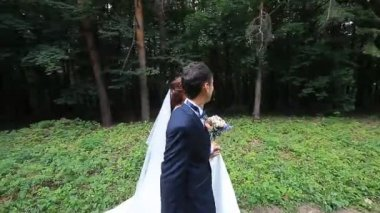 Beautiful bride and groom walk in the spring forest — Stock Video