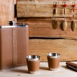 Hip metal flask, cups and knife on wooden background. — Stock Photo #68486743