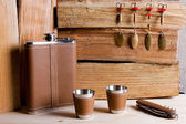 Hip metal flask, cups and knife on wooden background. — Stock Photo