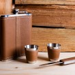 Hip metal flask, cups and knife on wooden background. — Stock Photo #69212665