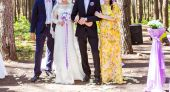 Happy bride and groom with guests — Stock Photo