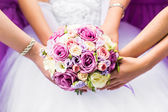 Close-up of a bride and her bridesmaids holding bouquet. — Stock Photo