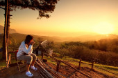 Woman watching sunset with a cup of warn drink — Stock Photo