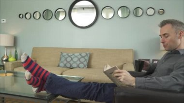 Man Reading Book in a Cozy Livingroom in 4K — Stock Video