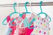 Row of little girl dresses hanging on coat hanger in white wardr — Stock Photo