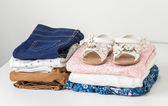 Stack of clean baby clothes in white wardrobe — Stock Photo