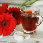 Black tea and beautiful flowers — Stock Photo #72927813