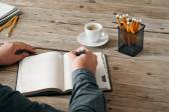 Ręka mężczyzny coś pisze w puste notatnik — Zdjęcie stockowe
