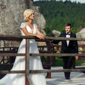 Groom comes to the bride standing near the fence on the mountain — Stock Photo