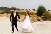 Bride and groom holding hands and running through the sand on th — Stock Photo