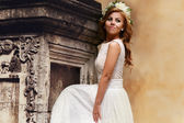Bride posing on the background wall — Stock Photo