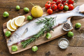 Fresh fish with vegetables on wooden board. Top view — Stock Photo