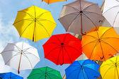 Bunten Schirmen gegen den Himmel in Stadt-Einstellungen. — Stockfoto