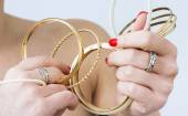 Woman's hands with gold bracelets — Stock Photo