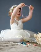 Beautiful little girl in white dress playing with jewelry — Stock Photo