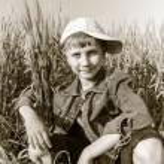 A little boy sitting in a wheat field among ears — Stock Photo #76388219