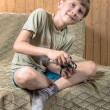 Boy plays with a joystick in Xbox — Stock Photo #77394414