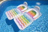 Colorful floating air mattresses in swimming pool at summertime — Stock Photo