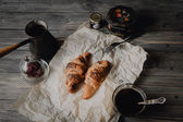 Croissants with chocolate and coffee on wood table — Stock fotografie