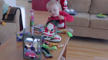 A little boy on christmas morning opening his stocking — Stock Video