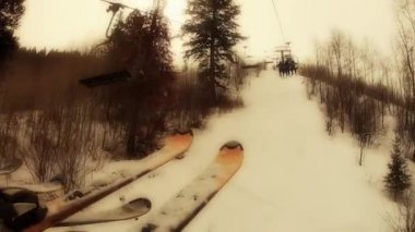 Skiers at a mountain resort on chair lift — Stock Video