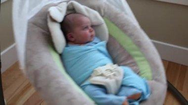 Cute newborn boy sitting in a swing — Stock Video