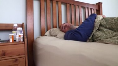 Sick man lying in his bed — Stok video