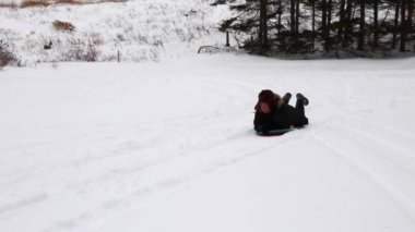 Woman sledding down hill — Stockvideo