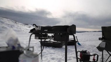Cooking food while ice fishing — Stock Video